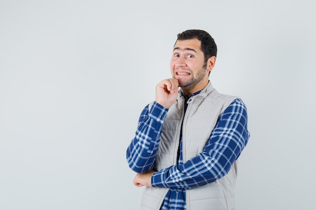 Молодой человек в рубашке, куртке без рукавов, выражая положительные эмоции и рад, вид спереди. место для текста
