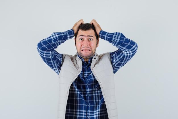 シャツを着た若い男、頭に手をつないで、問題を抱えているように見えるノースリーブのジャケット、正面図。