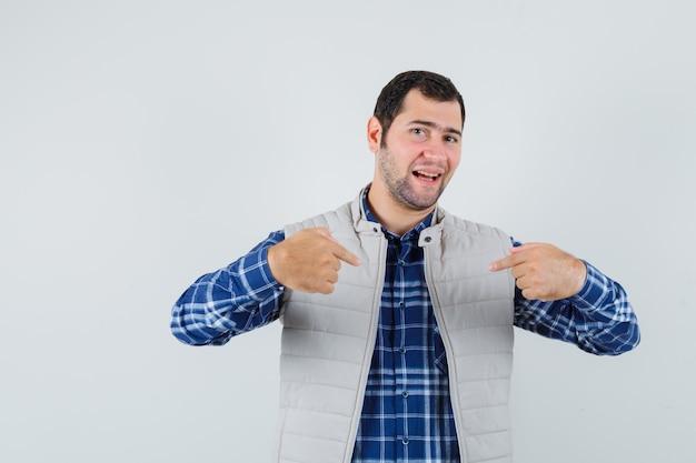 シャツを着た若い男、鼻をつまんでうんざりしているノースリーブのジャケット、正面図。