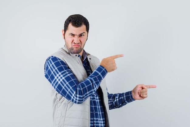 셔츠, 민소매 재킷 옆으로 가리키는 불쾌 하 게, 전면보기에 젊은 남자. 무료 사진