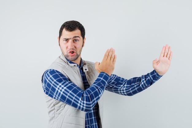 Молодой человек в рубашке, куртке без рукавов, демонстрирующей каратэ отбивной и выглядящей гибкой, вид спереди. Бесплатные Фотографии