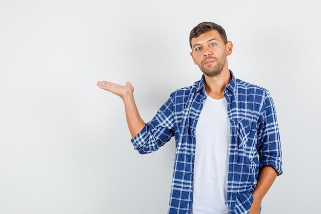 Молодой человек в рубашке разводит ладонь в сторону и выглядит строгим, вид спереди.