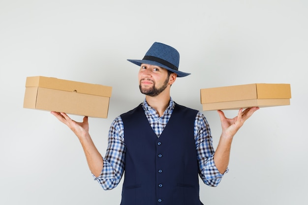 シャツ、ベスト、段ボール箱を保持し、自信を持って見える帽子、正面図の若い男。