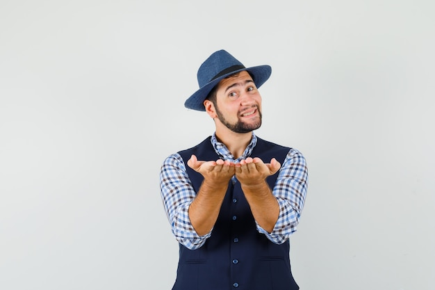 셔츠, 조끼, 모자를 받거나 제스처를주고 부드럽게 찾고있는 젊은 남자.