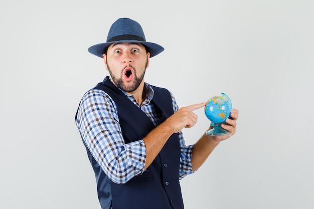 셔츠, 조끼, 모자 지구를 가리키고 놀랍게도, 전면보기에 젊은 남자.