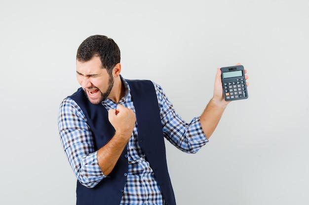 シャツを着た若い男、電卓を保持しているベスト