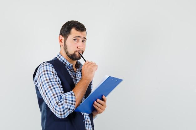 Молодой человек в рубашке, жилете с буфером обмена и ручкой и нерешительным взглядом, вид спереди.
