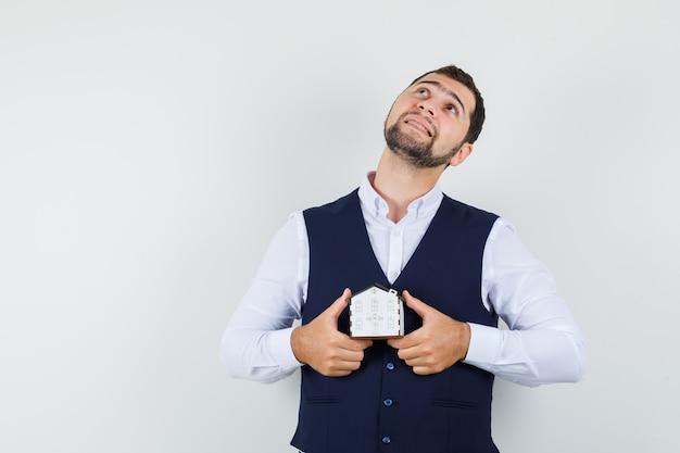 シャツを着た若い男、家のモデルを保持し、希望に満ちたベスト