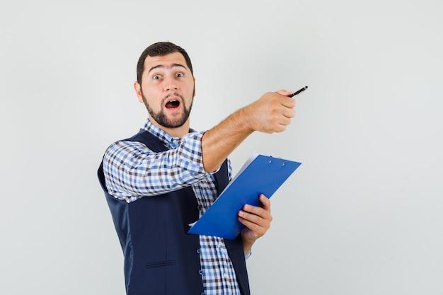 シャツを着た若い男、ペンを持ったベスト、クリップボード、向きを変えて驚いた様子、正面図。