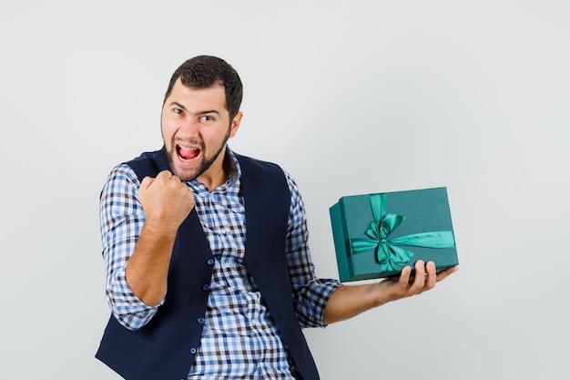 シャツを着た若い男、プレゼントボックスを保持しているベスト、勝者のジェスチャーを示し、幸せそうに見える、正面図。