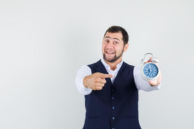 シャツを着た若い男、目覚まし時計を指して楽観的に見えるベスト