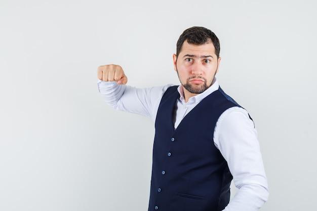 Молодой человек в рубашке, жилете угрожает кулаком и выглядит сильным