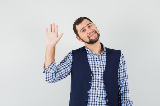 シャツを着た若い男、挨拶と陽気に見えるために手を振るベスト、正面図。