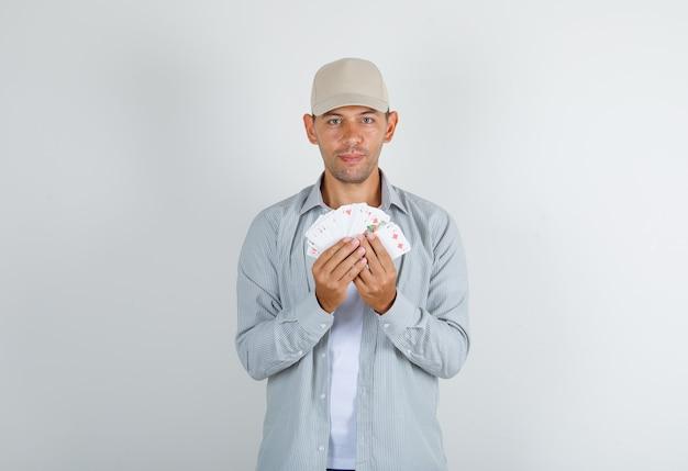 카드 놀이를 들고 웃 고 모자와 셔츠에 젊은 남자