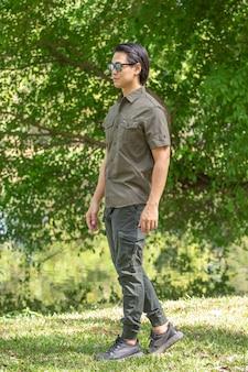 Молодой человек в рубашке с коротким рукавом и штанах стоит в парке