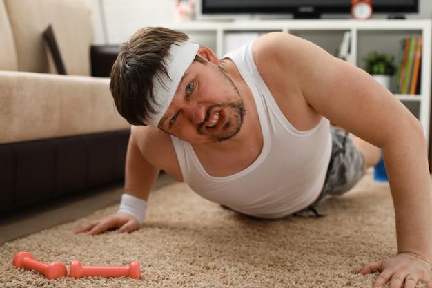 Молодой человек в шортах, упражнения дома
