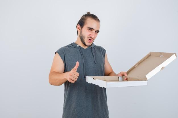 민소매 까마귀 지주에 젊은 남자가 엄지 손가락을 보여주는 동안 피자 상자를 열고 기쁘게, 전면보기를 찾고 있습니다.