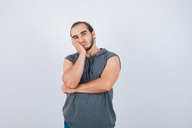 Молодой человек в толстовке с капюшоном без рукавов, держа руку на щеке и глядя задумчиво, вид спереди.