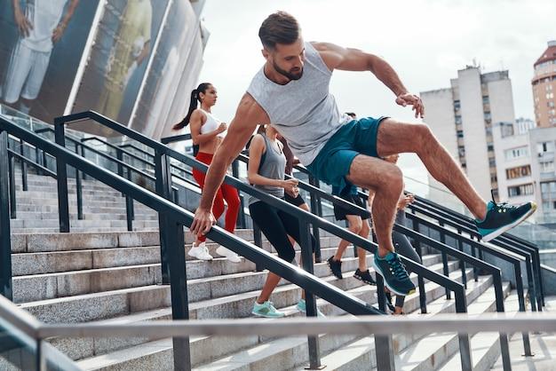 Молодой человек в спортивной одежде прыгает во время тренировки со своими друзьями на лестнице на открытом воздухе
