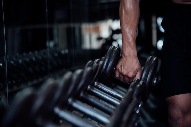 Молодой человек в спортивной одежде упражнения в тренажерном зале