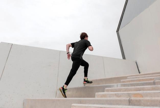 Молодой человек в спортивной одежде, упражнения на открытом воздухе