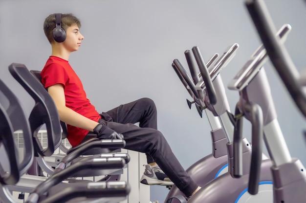 고정식 자전거에 체육관에서 운동복에서 젊은 남자