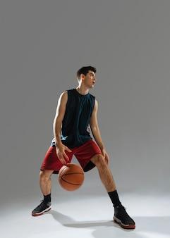 Молодой человек в спортивной одежде играет в баскетбол в одиночку