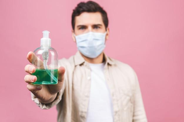 멸균 얼굴 마스크 고립에서 젊은 남자. 유행성 전염병 코로나 바이러스 2019-ncov sars covid-19 독감 바이러스 개념. 알코올 액체 항균 소독제 병.