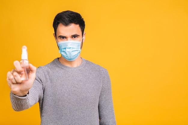 黄色の背景で隔離のポーズの滅菌フェイスマスクの若い男。