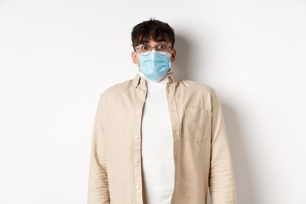 白い背景の上に立っているカメラに驚いて見えるcovidからの滅菌医療マスクの若い男...