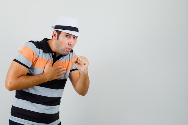 스트라이프 티셔츠, 모자 기침 및 텍스트에 대한 불편한 공간을 찾는 젊은 남자