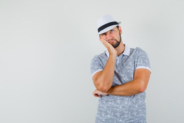 縞模様のtシャツを着た若い男、歯痛があり、問題を抱えているように見える帽子、正面図。テキスト用のスペース