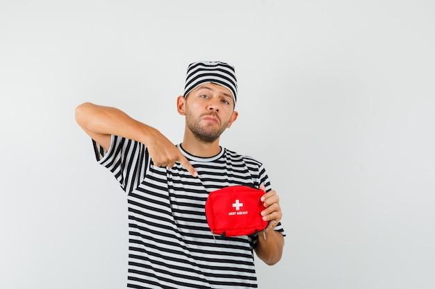 救急箱を指して自信を持って見える縞模様のtシャツの帽子をかぶった若い男