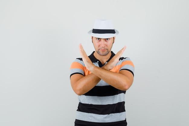 縞模様のtシャツを着た若い男、閉じたジェスチャーを示し、真剣に見える帽子