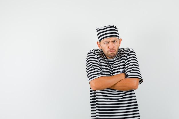 단단히 교차 팔을 서서 분개하게 보이는 스트라이프 티셔츠 모자에있는 젊은 남자