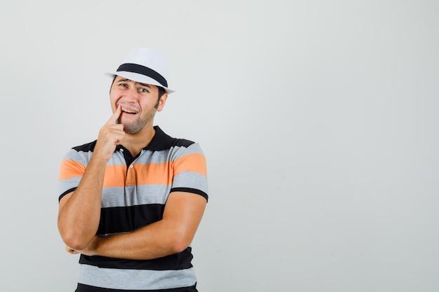 縞模様のtシャツを着た若い男、歯痛に苦しんでいて、テキストのための痛みを伴うスペースを探しています