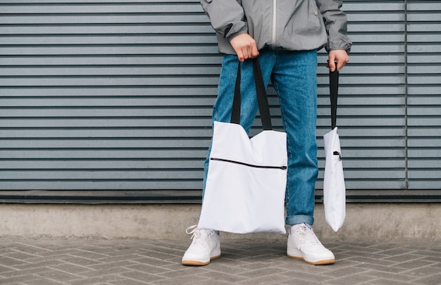 Молодой человек в стильной одежде стоит на сером фоне стены с эко сумками в руках на серой стене