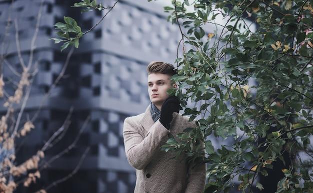秋の公園でスタイリッシュなコートを着た若い男