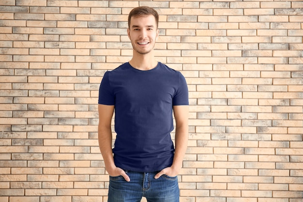 벽돌 표면에 세련 된 티셔츠에 젊은 남자. 디자인 목업