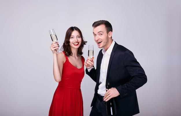 スーツの若い男と灰色の背景に分離されたシャンパングラスと赤いドレスの女性
