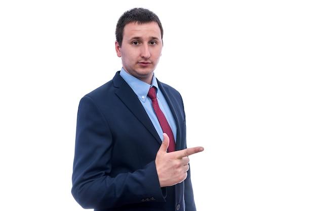 白い壁に隔離された身振りで示すスーツの若い男