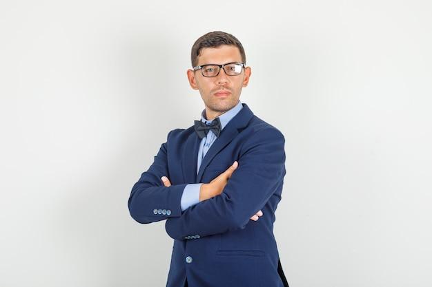 スーツを着た若い男、組んだ腕と立っていると自信を持ってメガネ