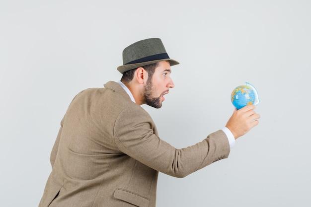 양복에 젊은 남자, 모자는 세계 세계를보고 집중 찾고.