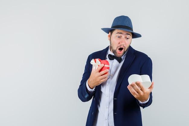 スーツを着た若い男、現在のボックスを見て、驚いて見える帽子、正面図。