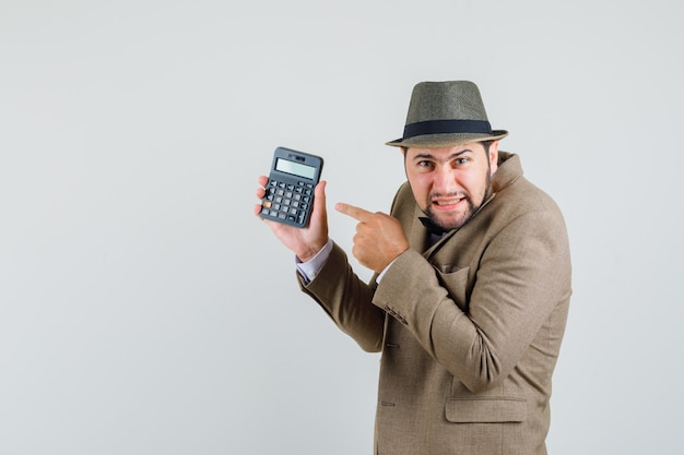 スーツを着た若い男、電卓を指して心配そうな帽子。