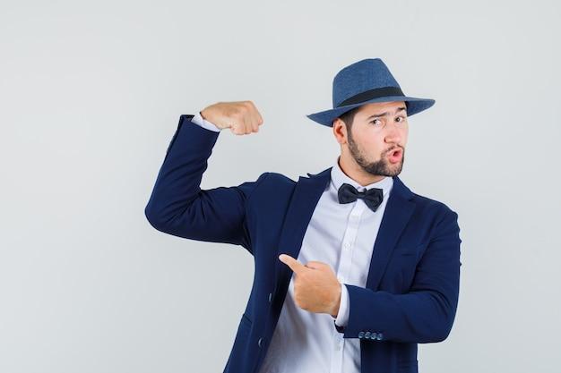 スーツを着た若い男、彼の筋肉を指して、自信を持って見える帽子、正面図。