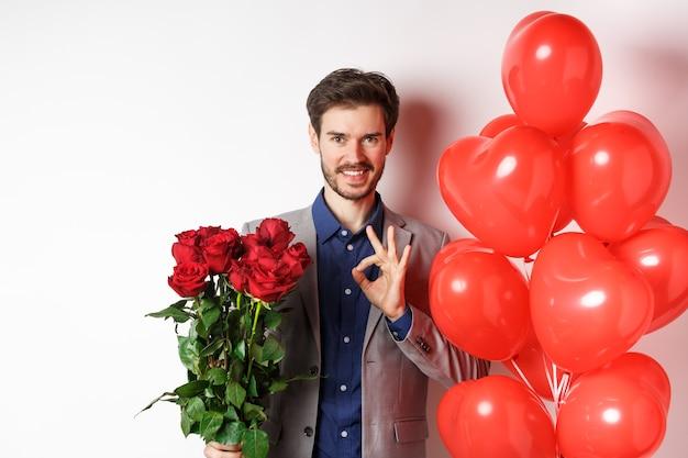 양복을 입은 젊은이는 모두 통제하에 확인 서명을 표시하고 빨간 장미를 들고 발렌타인 데이, 흰색 배경에 하트 풍선과 꽃으로 낭만적 인 놀라움을 준비합니다.