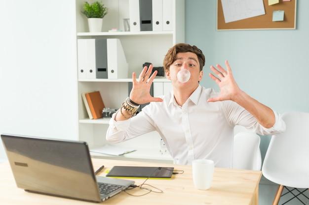 オフィスで楽しんでスーツを着た若い男