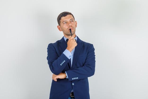 彼の唇にペンを押しながら物思いに沈んだ探しているスーツを着た若い男