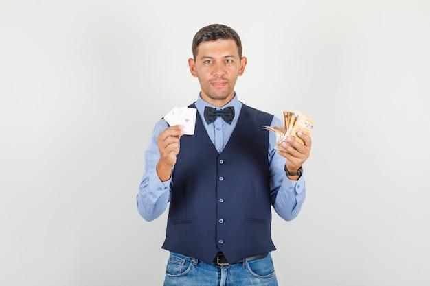 Молодой человек в костюме, джинсах держит банкноты евро и игральные карты и выглядит радостным